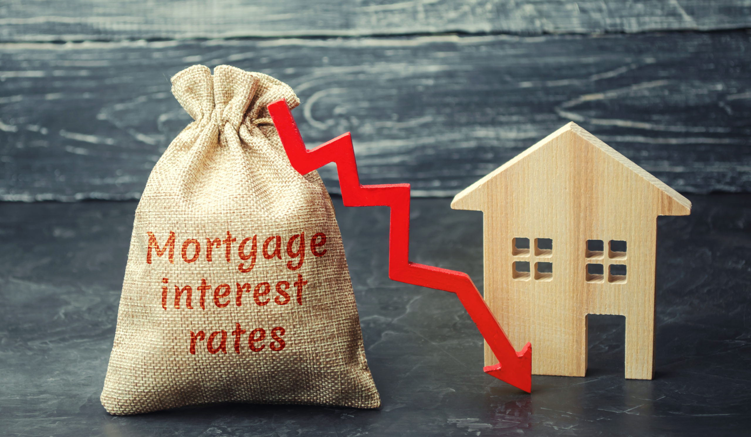 Bag with the money and the word Mortgage interest rates and arrow to down and house. Low interest in mortgages. Reducing interest payments for mortgages