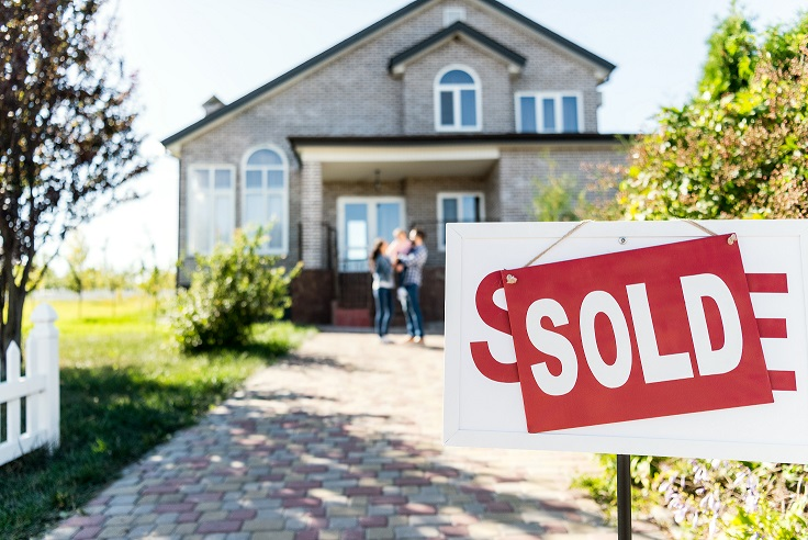 Couple stand in front of home with sold sign.